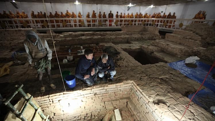 In this undated but recent photo released by National Geographic, archaeologists Robin Coningham, second from right, of Britain's Durham University and Nepalese archaeologist Kosh Prasad Acharya, right, direct excavations within the Mayadevi Temple, uncovering a series of ancient temples contemporary with the Buddha as Thai monks meditate in the background. Buddha, also known as Siddhartha Gautama, is generally thought to have been born in about the sixth century B.C. at the temple site. (AP Photo/National Geographic, Ira Block) MANDATORY CREDIT