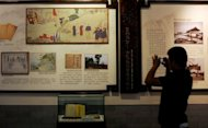 "A visitor takes a picture of the drawings that depict Ryukyu students' school life in the ancient Imperial College as they are displayed at the Imperial College in Beijing on October 10, 2012. In recent anti-Japan protests in China, some demonstrators carried signs reading: ""Retake Ryukyu"" and ""Take back Okinawa"""