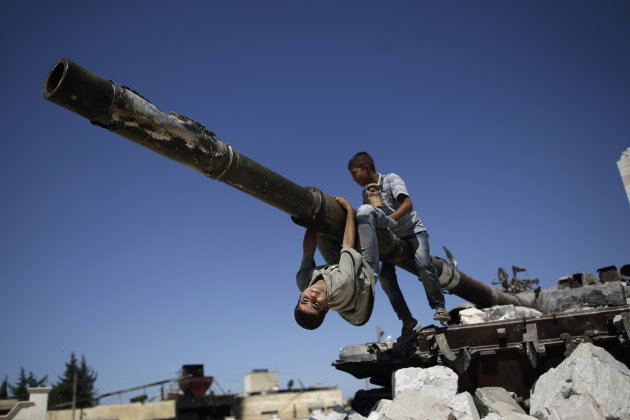 A boy looks back while he and another boy play on a Syrian military tank, destroyed during fighting with the Rebels, in the Syrian town of Azaz, on the outskirts of Aleppo, Sunday, Sept. 2, 2012.