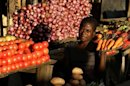 A girl poses for a photographer at her vegetable stall in Tsangano
