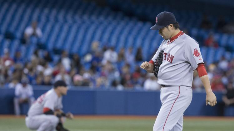 Boston Red Sox pitcher Junichi Tazawa reacts after Toronto Blue Jays' Kevin Pillar hits a double during seventh inning American League baseball action in Toronto on Wednesday, Aug. 27, 2014. (AP Photo/The Canadian Press, Chris Young)