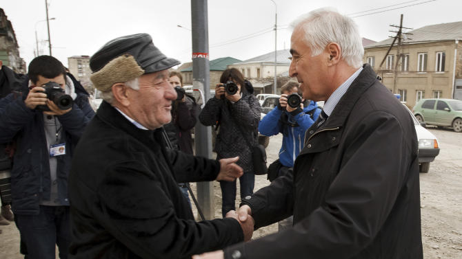 Presidential candidate former local KGB chief Leonid Tibilov, right, shakes hands with a local resident after voting at the polling station in Tskhinvali in Georgia's breakaway province of South Ossetia , Sunday, March 25, 2012. Georgia's breakaway province of South Ossetia is again trying to elect a president after a disputed November election ended in scandal. Four candidates are running in Sunday's election, and none is considered the clear favorite. Neither the winner of the November election, Alla Dzhioyeva, nor her Kremlin-backed rival were allowed to run. (AP Photo/Ignat Kozlov)