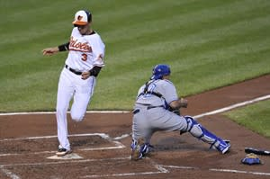 Baltimore Orioles Ryan Flaherty scores after being singled in by Manny Machado as Toronto Blue Jays catcher Henry Blanco awaits the throw in the second inning of a baseball game Tuesday, April 23, 2013 in Baltimore. (AP Photo/Gail Burton)