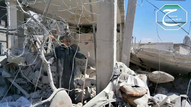 This citizen journalism image provided by Qusair Lens, which has been authenticated based on its contents and other AP reporting, shows a Syrian man checking his destroyed house that was damaged by a Syrian forces air strike in the town of Qusair, near the Lebanon border, Homs province, Syria, Tuesday, May 21, 2013. Several members of Lebanon's militant Hezbollah group died of wounds sustained while fighting for control of a strategic Syrian town near the Lebanese border, activists said Tuesday, as the battle in the area raged for its third straight day. (AP Photo/Qusair Lens)