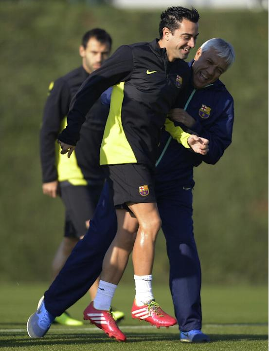 FC Barcelona's Xavi Hernandez, left, and physical trainer Elvio Paolorosso share a light moment during a training session at the Sports Center FC Barcelona Joan Gamper in San Joan Despi, Spain, Tu