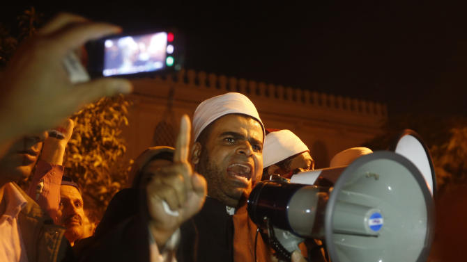 A cleric from Al-Azhar, Egypt's most respected Islamic institution, addresses protesters in front of the presidential palace during a demonstration in Cairo, Egypt, Tuesday, Dec. 11, 2012. Thousands of opponents and supporters of Egypt's Islamist president staged rival rallies in the nation's capital Tuesday, four days ahead a nationwide referendum on a contentious draft constitution. (AP Photo/Petr David Josek)