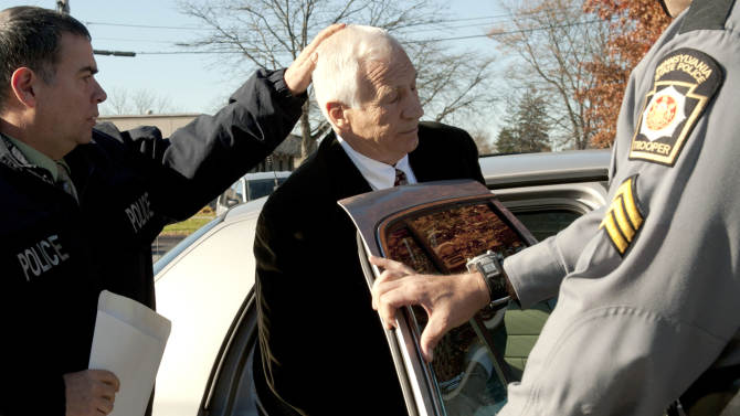 """In this photo provided by the Pennsylvania Office of Attorney General, former Penn State football defensive coordinator Gerald """"Jerry"""" Sandusky, center, is placed in a police car iin Bellefonte, Pa. to be taken to the office of a Centre County Magisterial District judge on Saturday, Nov. 5, 2011. Sandusky is charged with sexually abusing eight young men. Also, Penn State athletic director Tim Curley and Penn State vice president for finance and business Gary Schultz, 62, are expected to turn themselves in on Monday on charges of perjury and failure to report under Pennsylvania's child protective services law in connection with the investigation into the abuse allegations against Sandusky. (AP Photo/Pennsylvania Office of Attorney General, Commonwealth Media Services)"""