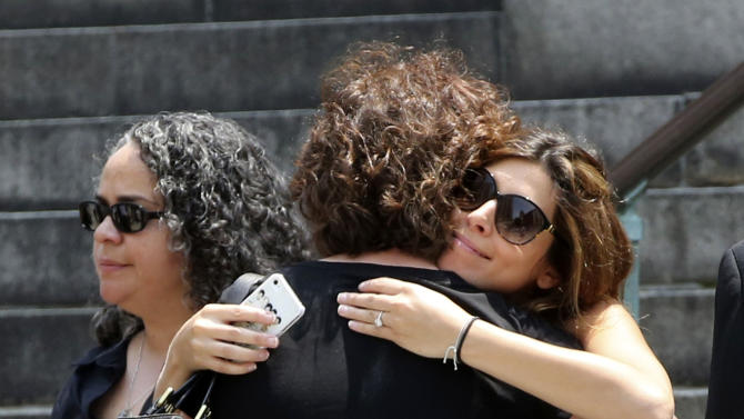"""Actress Jamie Lynn Sigler, right, is embraced as she leaves the Cathedral Church of Saint John the Divine after the funeral service for James Gandolfini, Thursday, June 27, 2013 in New York. Gandolfini, who played Tony Soprano in the HBO show """"The Sopranos"""", died while vacationing in Italy last week. (AP Photo/Mary Altaffer)"""