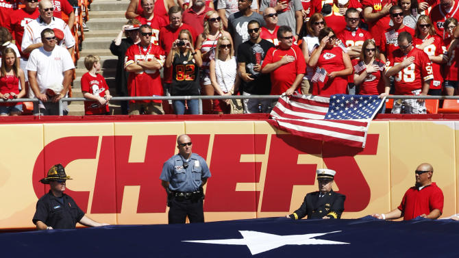 First responders hold an American flag before an NFL football game between the Buffalo Bills and Kansas City Chiefs at Arrowhead Stadium, Sunday, Sept. 11, 2011, in Kansas City, Mo. The day marks the 10th anniversary of the 9/11 attacks. (AP Photo/Orlin Wagner)