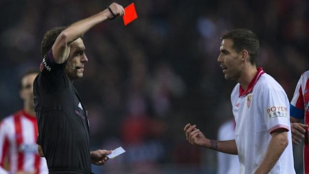 Sevilla's Fenando Navarro is shown a red card during the Copa del Rey semi-final first-leg against Atletico de Madrid (AFP)