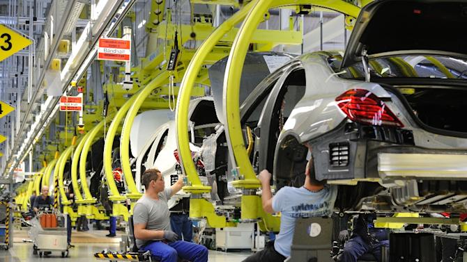 Workers instal parts on Mercedes-Benz S-class passenger cars on the production line at the Mercedes-Benz factory of the Daimler AG in Sindelfingen, southwest Germany, on January 24, 2014