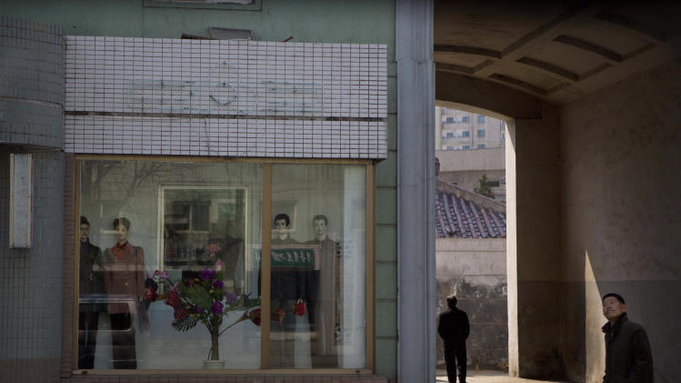 North Korean men walk along a street in front of a clothing store in Pyongyang on Friday, April 12, 2013. (AP Photo/David Guttenfelder)