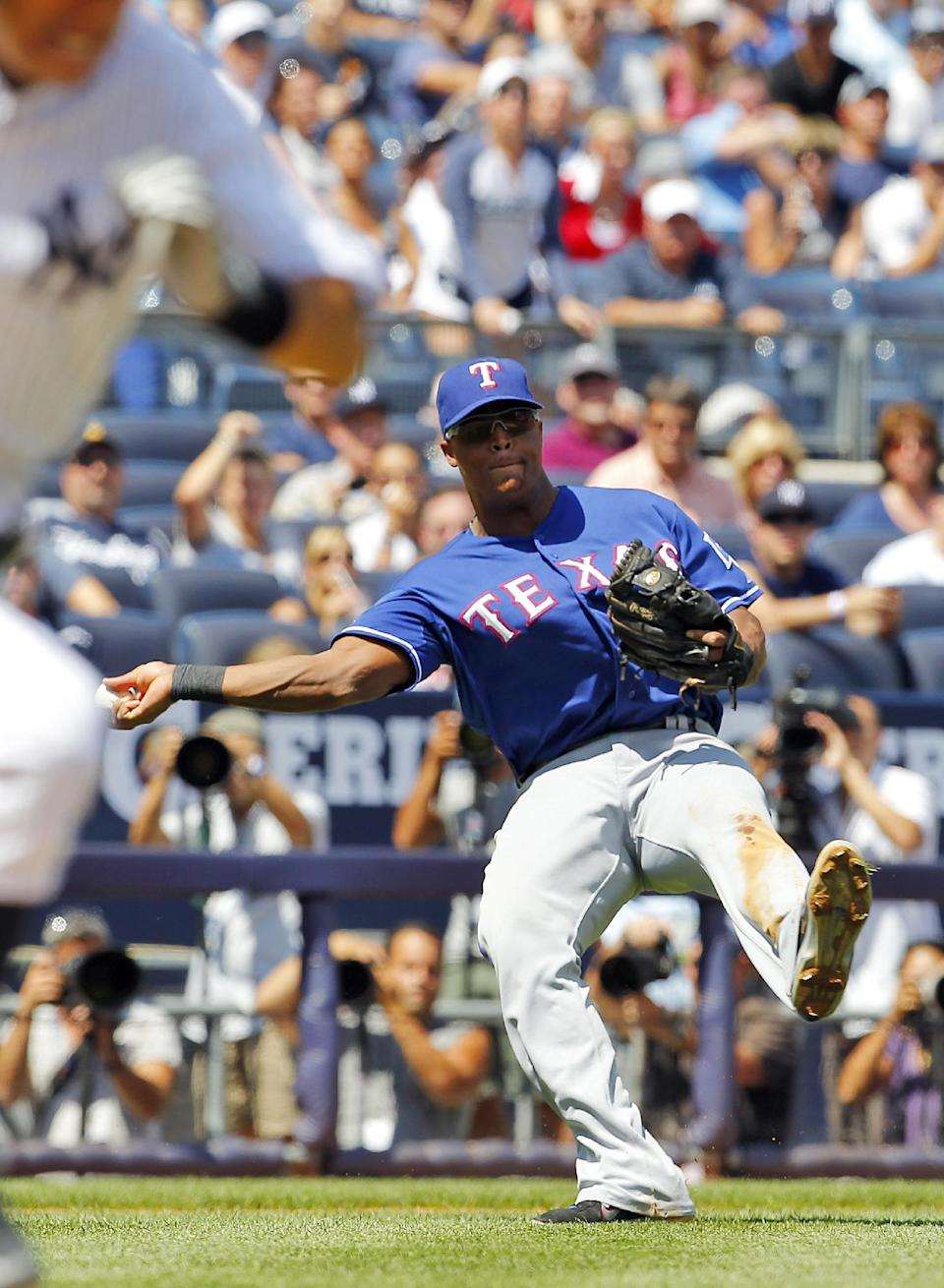 Texas Rangers' Adrian Beltre falls backward as he throws out New York Yankees' Ichiro Suzuki running to first base on a sacrifice bunt in the third inning of a baseball game at Yankee Stadium in New York, Thursday, Aug. 16, 2012. (AP Photo/Paul J. Bereswill)