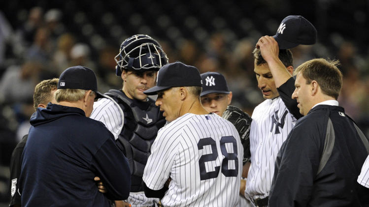 New York Yankees pitcher Andy Pettitte, second from right, reacts as manager Joe Girardi (28) talks with pitching coach Larry Rothschild as Pettitte is taken out of the baseball game during the fifth inning of against the Seattle Mariners, Thursday, May 16, 2013, at Yankee Stadium in New York. (AP Photo/Bill Kostroun)