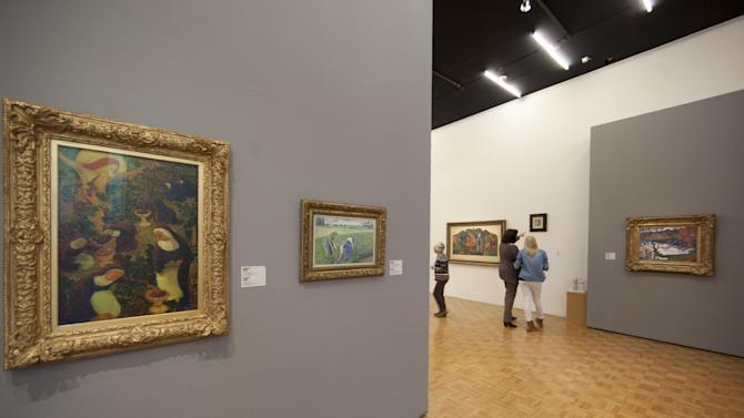 """""""Peasant Women Working in the Fields"""" by Camille Pissarro, second painting from left, now hangs in place of the stolen Henri Matisse painting at Kunsthal museum, as the museum reopened its doors to the public following Tuesday morning's major art heist in Rotterdam, Wednesday Oct. 17, 2012. Police investigating a multimillion euro (dollar) art heist say they are following up several tips from the public, a day after thieves grabbed seven paintings from the walls of a Rotterdam gallery and vanished into the night. A spokeswoman for detectives on the case, Willemieke Romijn, said Wednesday they have some 15 tips from the public, following a late-night, nationally televised appeal for witnesses to the theft from the Kunsthal gallery of works by celebrated artists including Pablo Picasso, Claude Monet and Henri Matisse. (AP Photo/Peter Dejong)"""