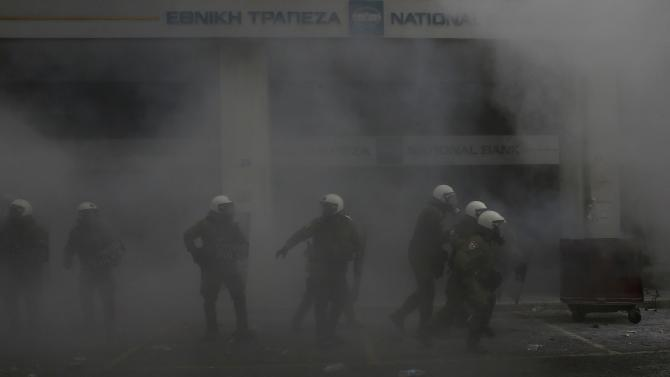 Greek police are seen amidst smoke from a tear gas during a protest of farmers against planned pension reforms outside the Agriculture ministry in Athens