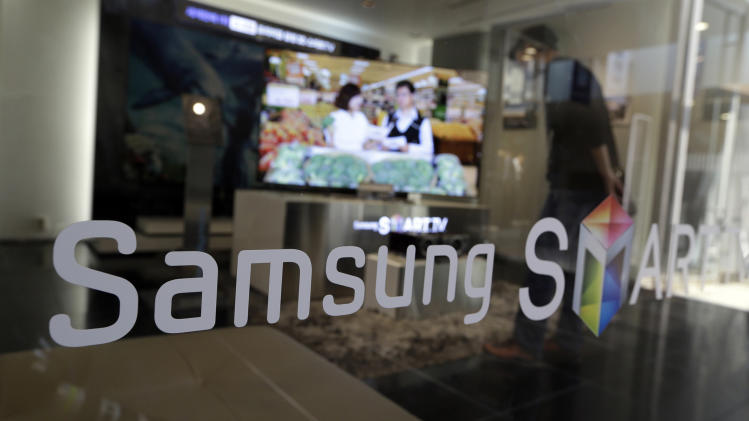 A man watches a movie on a Samsung Electronics's product at a showroom of its headquarters in Seoul, South Korea, Friday, Oct. 5, 2012. Samsung Electronics Co. tipped all-time high quarterly operating profit, likely driven by strong sales of high-end smartphones that offset weak semiconductor orders. (AP Photo/Lee Jin-man)
