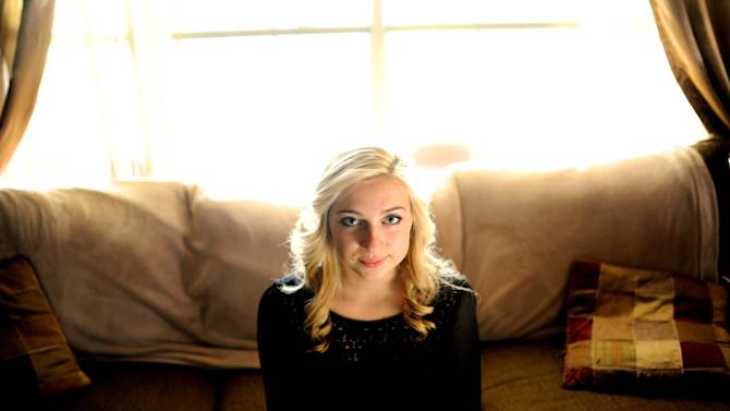 """Sarah Ball, a victim of cyber bullying during her high school years, sits for a portrait at her home on Wednesday, Oct. 23, 2013, in Spring Hill, Fla. Ball, now a student at a nearby community college, maintains a Facebook site called """"Hernando Unbreakable"""", an anti-bullying page and mentors local kids identified by the schools as victims of cyberbullying. (AP Photo/Brian Blanco)"""