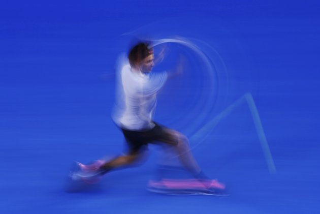 Roger Federer of Switzerland hits a return to Andy Murray of Britain during their men's singles semi-final match at the Australian Open tennis tournament in Melbourne