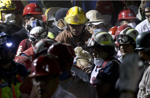 Rescue workers and firefighters carry an injured person after an explosion in a building at Mexico's state-owned oil company PEMEX complex, in Mexico City, Thursday Jan. 31, 2013. The explosion killed