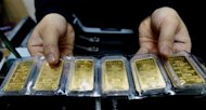 An employee holds gold bars in Hanoi. Limiting widespread street-level trading of gold will, the official line goes, reduce price volatility and prevent retail investors from pouring into the precious metal, which undermines the already-shaky dong