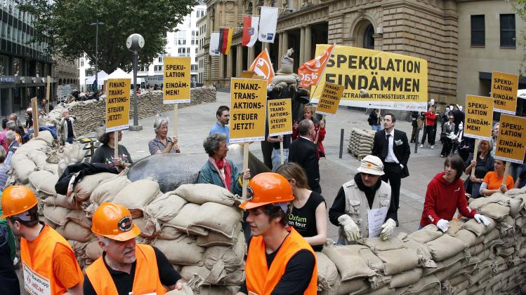 "In this picture taken with a fisheye lens, protesters,  build a wall around the Frankfurt stock exchange with  sandbags to demonstrate against sthe current financial policy in Frankfurt, central Germany, Sunday June 17, 2012. Poster at right reads: Stem Speculations,  and  others : Transaction Tax  Now.   Activists calling for a tax on financial transactions have erected a wall of sandbags outside the Frankfurt stock exchange.The anti-globalization group Attac said that about 200 people participated in Sunday's action. Carrying placards with slogans such as ""Stem Speculation"" and ""Financial transaction tax now,"" they built the wall of sandbags around the statues of a bull and a bear symbols of optimistic and pessimistic markets  that stand in front of the exchange building. (AP Photo/dapd/mario Vedder)"