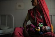 A new born baby sleeps in the arms of her mother at a Community Health Center in Mall, near the central east Indian city of Lucknow on October 31, 2011. Mounting concern over humanity's environmental impact and fears we may not be able to feed ourselves in 100 years' time have cast a cautionary tone over the buildup to the seven billion milestone