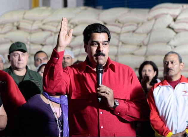 "In this photo provided by Miraflores Presidential Press Office, Venezuela's Vice-President Nicolas Maduro, center, delivers a speech during a visit to ""Fama de America"" government-run coffee plant in"