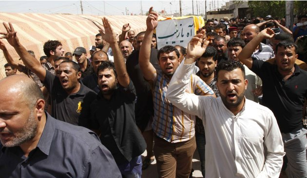 File photo of Iraqi mourners chanting slogans as they carry coffin of Shi'ite militia fighter killed in clashes with Free Syrian Army, during  funeral in Basra
