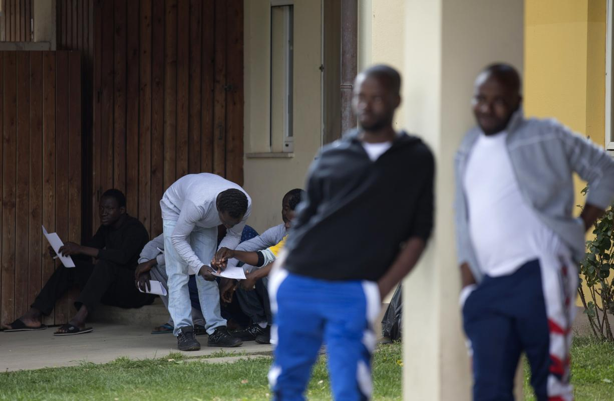 Migrants and asylum seekers look at papers in the Mineo center, Tuesday, April 21, 2015, in Sicily, Italy. The United Nations refugee agency said Tuesday that more than 800 people were believed to have drowned in the weekend sinking of a boat packed with migrants trying to reach Europe, making it the deadliest such disaster in the Mediterranean. Survivors of the shipwreck were taken to Mineo, the largest center in Sicily, hosting nearly 4,000 people. (AP Photo/Alessandra Tarantino)
