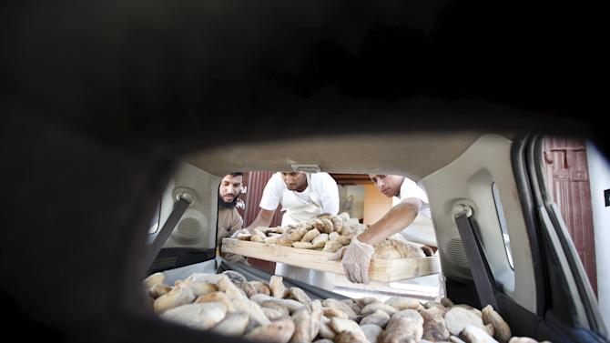 Workers load bread on a car for distribution from the Bunian charitable bakery in Yemen's capital Sanaa