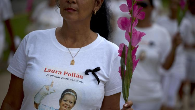 "A member of Cuba's Ladies in White dissident group, wearing a T-shirt with an image of the late co-founder of the group, Laura Pollan, participates in a march marking one year since the death of Pollan in Havana, Cuba, Sunday, Oct 14, 2012. The Ladies in White was formed in 2003 mostly by wives and family members of 75 dissidents jailed in a crackdown on dissent. Pollan had been married to one of the dissident prisoners, Hector Maseda. The T-shirt reads in Spanish ""you stay with us."" (AP Photo/Ramon Espinosa)"