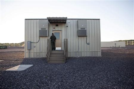 A border patrol agent opens the entrance to a temporary holding facility at the U.S. Department of Homeland Security's FOB Hedglen located southeast of Douglas