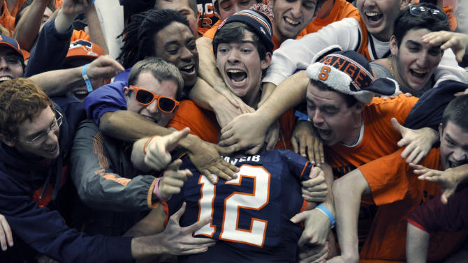 Syracuse quarterback Ryan Nassib celebrates with fans after Syracuse defeated Louisville 45-26 in an NCAA college football game in Syracuse, N.Y., Saturday, Nov. 10, 2012. (AP Photo/Kevin Rivoli)