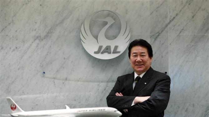 Yoshiharu Ueki, president of Japan Airlines, poses for photographs with a model of JAL's Airbus A350-900 after an interview with Reuters at its headquarters in Tokyo