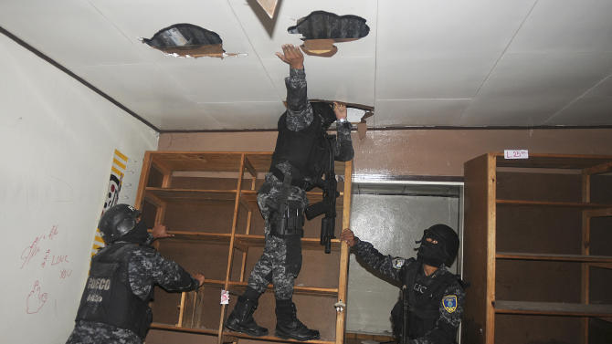 In this June 14, 2012 photo, national police inspect a home that had been seized by gangs in the 14 de Marzo neighborhood in Tegucigalpa, Honduras. Gang members seized the home after the rightful owners fled, unable to pay their extortion fees.  Extortion of homeowners is a chilling new crime trend in Honduras, already among the world's most dangerous countries. By demanding people pay to stay in their own homes, gang members have emptied some neighborhoods and have changed the way many live.  (AP Photo/Fernando Antonio)