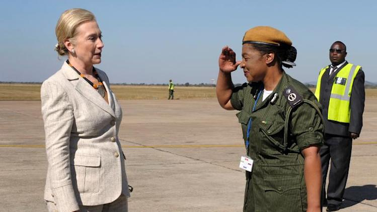 US Secretary of State Hillary Rodham Clinton is saluted by Mary Tembo, then commanding officer of the Zambian National Police at Lusaka International Airport in Lusaka, Zambia, on June 11, 2011