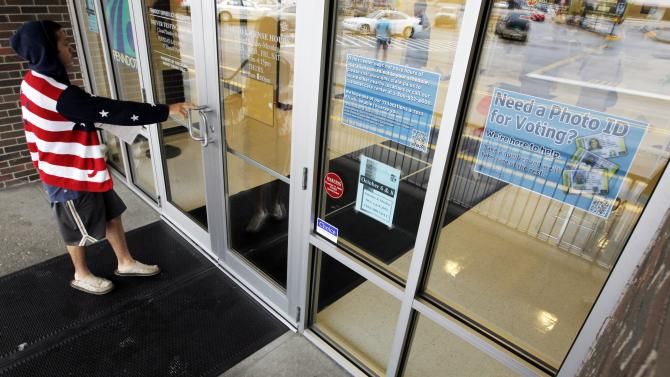 FILE - In this Sept. 26, 2012 file photo, A man heads into the the Penndot Drivers License Center in Butler, Pa., near a sign telling of the requirement for voters to show an acceptable photo ID to vote.  Some political momentum could be on the line in a judge's forthcoming ruling on Pennsylvania's tough new voter identification law. Commonwealth Court Judge Robert Simpson is expected to rule Tuesday. That's just five weeks before voters decide whether to re-elect President Barack Obama, a Democrat, or replace him with Mitt Romney, a Republican. (AP Photo/Keith Srakocic, File)
