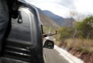 A vigilante aims his weapon out of a car window while driving in a convoy with others to Poturo