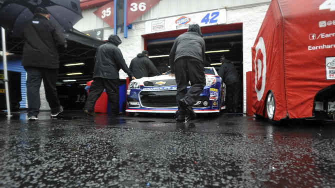 Pit crew members push the car of driver Juan Pablo Montoya into the Grand National Garage at Talladega Superspeedway in Talladega, Ala., Saturday, May 4, 2013. Rain threatens Saturday's qualifying for Sunday's NASCAR Sprint Cup series Aaron's 499 auto race. (AP Photo/Rainier Ehrhardt)