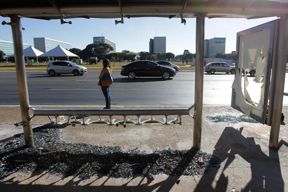 A bus stop's window lays shattered below the seats after protests in Brasilia, the capital of Brazil, Friday, June 21, 2013. Police and protesters fought in the streets into the early hours Friday in the biggest demonstrations yet against a government viewed as corrupt at all levels and unresponsive to its people. (AP Photo/Eraldo Peres)