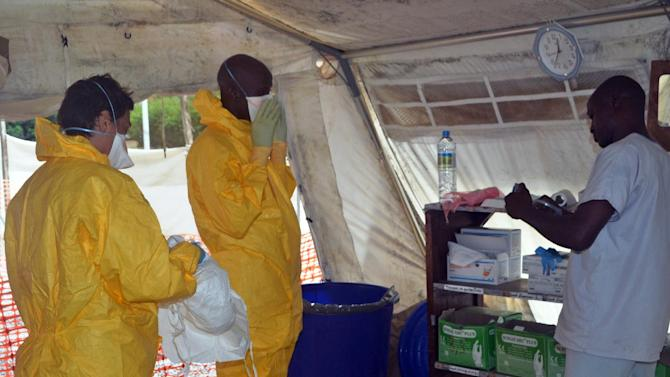 Medics put on protective gear at the isolation ward of the Donka hospital, on July 23, 2014 in Conakry, where patients are being treated for Ebola