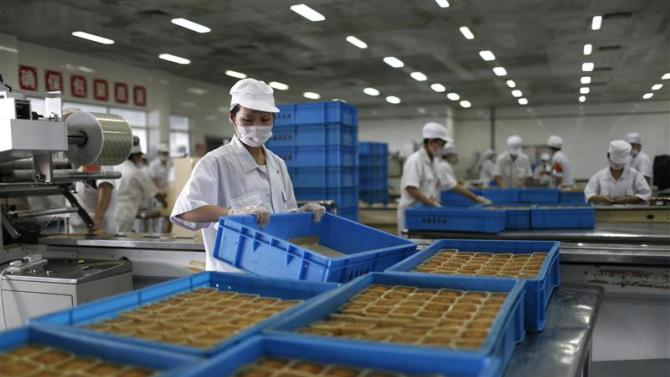 Feshly-baked mooncakes pass along a conveyor belt at a mooncakes factory in Shanghai