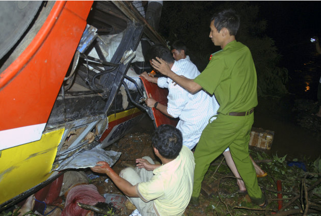 In this photo taken on Thursday, May 17, 2012, rescuers work to search for victims of a bus accident in central highland province of Dak Lak, Vietnam. The crowded bus plunged into a river bank, killin