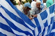 Supporters of Greek conservative party New Democracy distribute flags prior to a pre-election speech of their leader Antonis Samaras in Athens on May 3. Not only Greece but also Europe braced for an election that polls indicate will fail to produce a clear winner, and which markets worry will plunge the eurozone into fresh turmoil