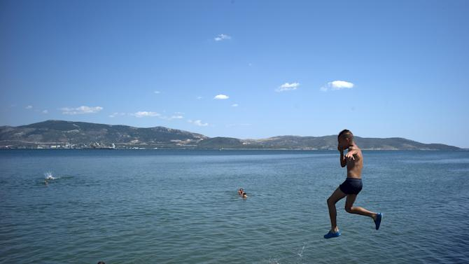 Youths swim at the beach of Elefsina, near Athens, Greece