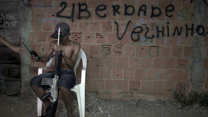 """In this photo taken Dec. 8, 2012, a young drug dealer sitting on a chair holds a weapon and a two-way radio at a slum in western Rio de Janeiro, Brazil. The South American country began experiencing a public health emergency in recent years as demand for crack boomed and open-air """"cracolandias,"""" or crack lands, popped up in the sprawling urban centers of Rio and Sao Paulo, with hundreds of users gathering to smoke the drug. The federal government announced in early 2012 that more than $2 billion would be spent to fight the epidemic, with the money spent to train local health care workers, purchase thousands of hospital and shelter beds for emergency treatment, and create transitional centers for recovering users. The graffiti reads in Portuguese """"Freedom old man."""" (AP Photo/Felipe Dana)"""
