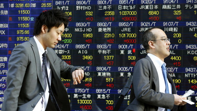 FILE - In this Thursday, Feb. 28, 2013, photo, a man looks at his watch while walking in front of an electronic stock indicator in Tokyo. U.S. stocks are not alone in racing ahead this year. Many markets in Europe and Asia are trading at multi-year highs, too, in part because of Wall Street's rally. (AP Photo/Shizuo Kambayashi, File)