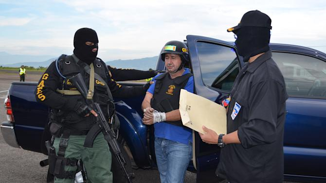 """In this photo provided by the Ministry of Popular Power for Interior Relations and Justice, Venezuela's judicial police officers escort alleged Colombian drug trafficker Daniel Barrera, center, at the Regional Command No. 1 National Guard base in San Cristobal, Tachira state, Venezuela, Wednesday, Sept. 19, 2012.  Colombia's President Juan Manuel Santos announced Tuesday evening that a man he described as Colombia's last big-time drug lord had been captured in neighboring Venezuela. It was the third arrest of a purported Colombian drug boss in the last year. Santos said alleged drug boss Daniel """"Loco"""" Barrera was arrested in the Venezuelan city of San Cristobal after months of multinational cooperation that included help from the U.S. and other nations. (AP Photo/Ministry of Popular Power for Interior Relations and Justice)"""