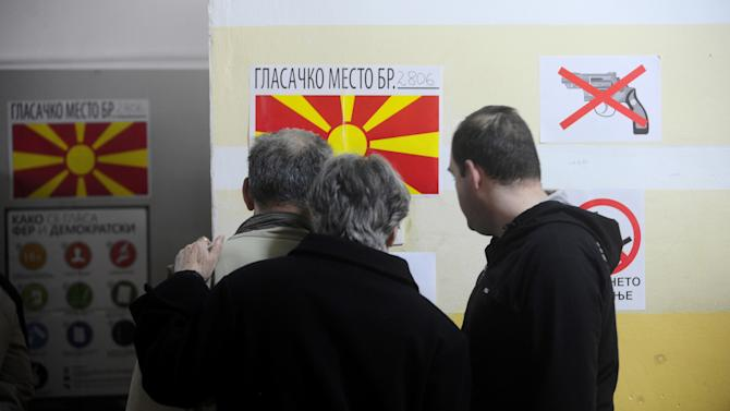 People check for their polling place to vote in local elections at a polling station in Skopje, Macedonia, on Sunday, March 24, 2013. The small Balkan country hopes that free, transparent and peaceful local elections will help it strengthen its case for European Union membership. (AP Photo/Boris Grdanoski)